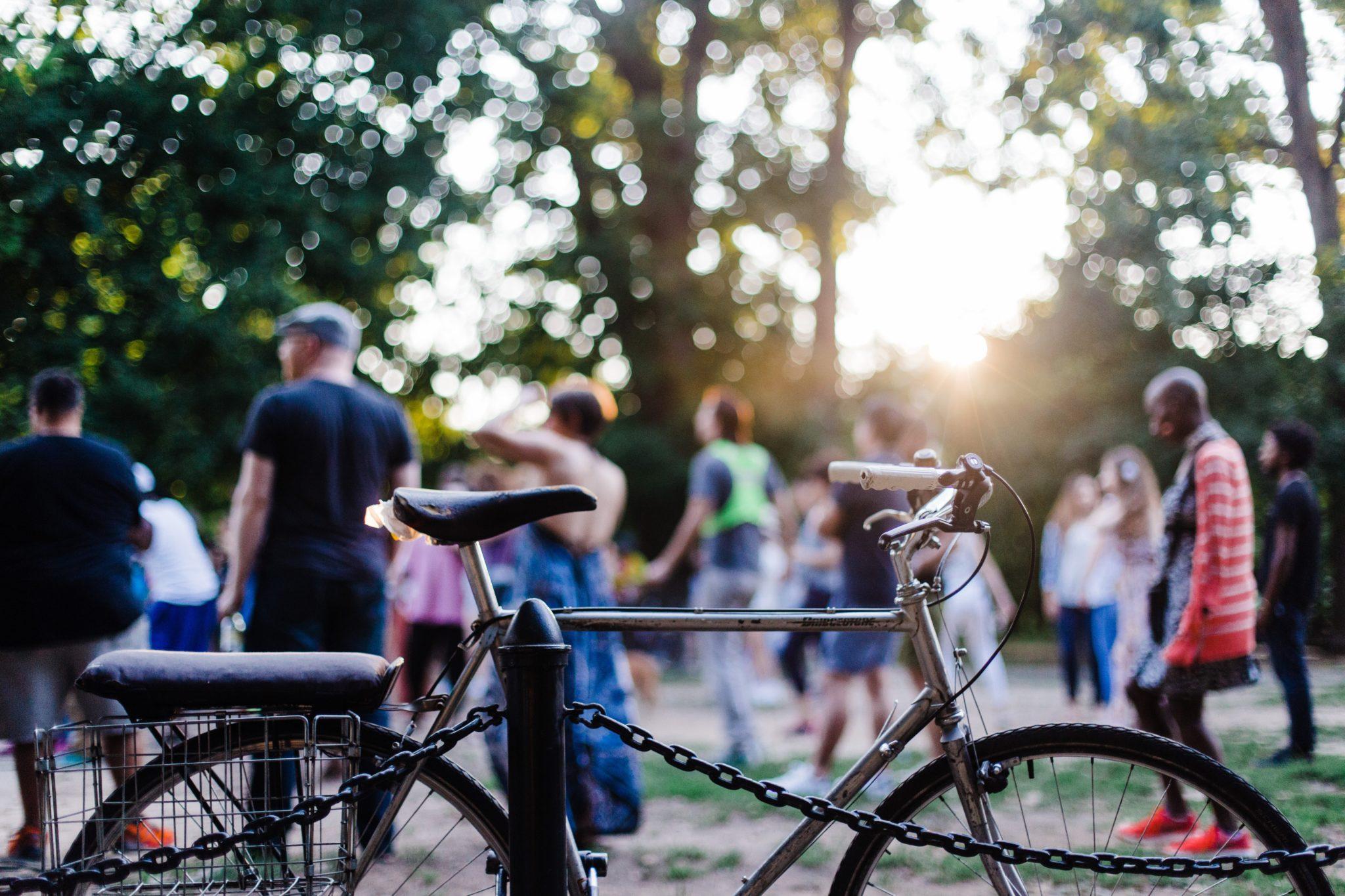 En cykel står mot räcke med folk i bakgrunden